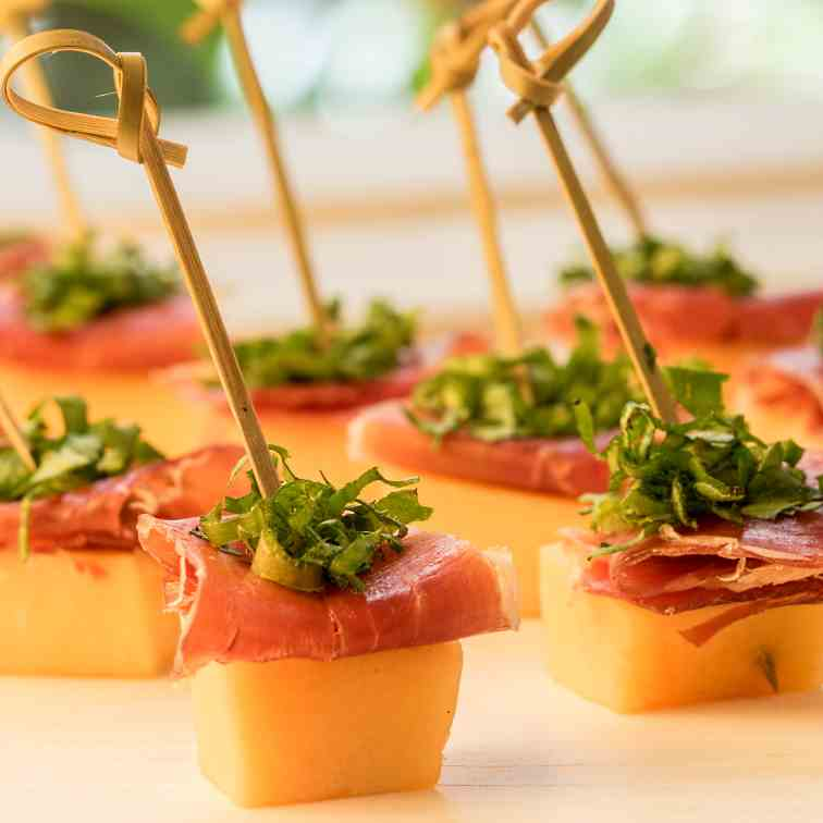Melon - Prosciutto Skewers over Greens Mix